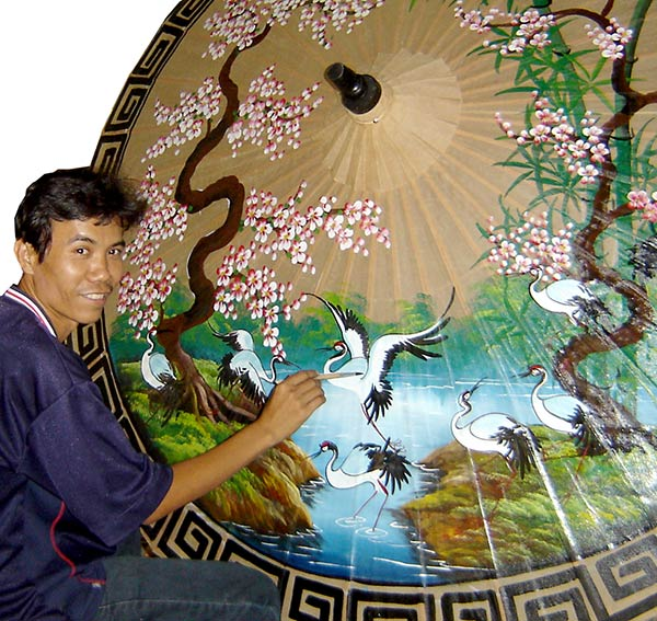 Artist painting a large umbrella.