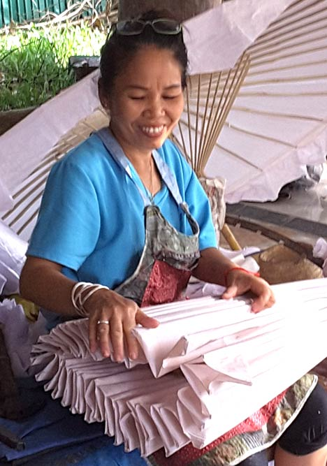 Folding the pleats of the umbrella by hand