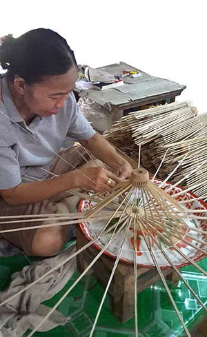 Craftsman hand stitching the bamboo ribs of an umbrella